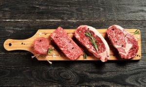 Steaks on wooden platter