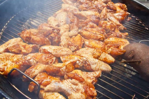 BBQ chicken wings cooking on a hot grill